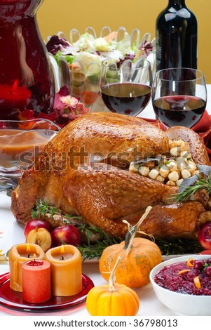 Garnished roasted turkey on holiday decorated table with pumpkins and glasses of red wine
