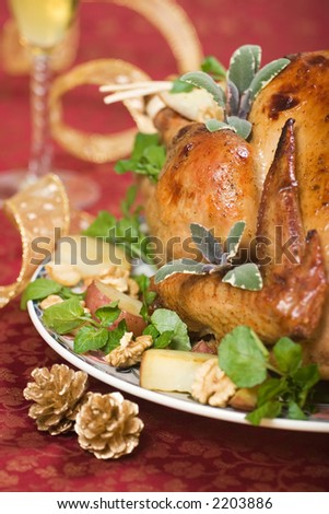 Garnished turkey on Christmas decorated table with flute of champagne on background