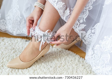 Garter on the leg of a bride, slim sexy bride in wedding luxury dress showing her silk garter. Woman have a final preparation for wedding ceremony