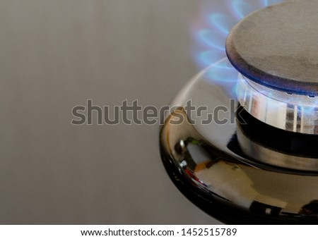 Gas burner with a burning flame on the stove with a glass surface. Kitchen equipment for cooking. Cropped front picture from above at a slight angle
