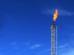 Gas flare is releasing and burning to the atmosphere at an offshore gas platform with sky. Fire on a stack of flare at oil and gas central processing platform. A gas flare at an oil refinery.
