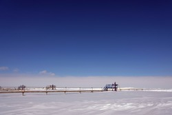 Gas industry, hydrocarbon production. A bush of gas wells against the background of a snow cover. Overall plan
