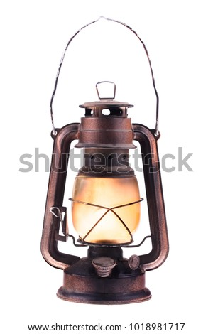 Gas lantern with burning light, isolated on a white background. An antique vintage lamp. Hipster accessory. Camping light. Interior decoration. Rusty, covered with patina. Wire handle #1018981717