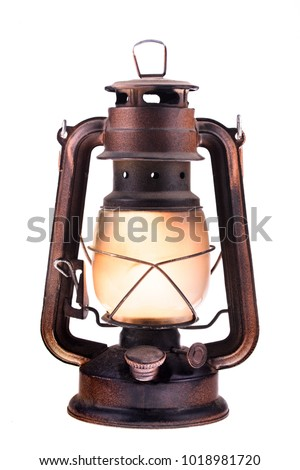 Gas lantern with burning light, isolated on a white background. An antique vintage lamp. Hipster accessory. Camping light. Interior decoration.  Rusty, covered with patina. Metal case, smoked frosted