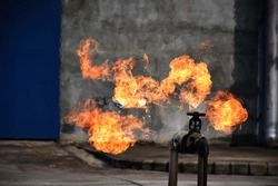 gas leak from pipe and valv.Flame from Gas leak.fire fighting with extingguishers and fire hose.Fighters in Action at Gas Fire and training