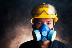 Gas mask. Respirator cartridge. Man in factory with backdrop - close up