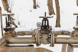 Gas pipes and valves in a snowy forest