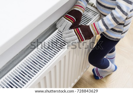 Gas powered central heating radiator at home. A child in woolen gloves and a sweater warms his hands near the heater.