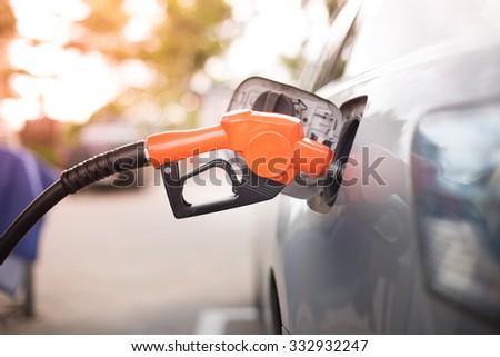 Gas pump nozzle in the fuel tank of a bronze car, refuel