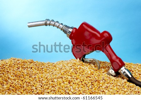 Gas pump sits in a pile of golden corn kernals with space for copy