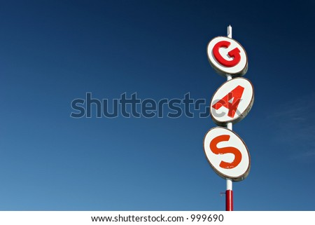 gas sign retro style, red white and blue, against blue sky with plenty of copyspace.