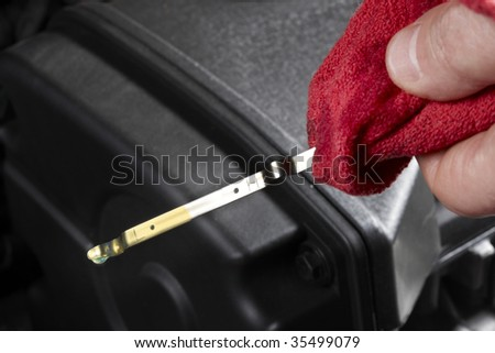 Gas station attendant, holding red rag, checks oil level