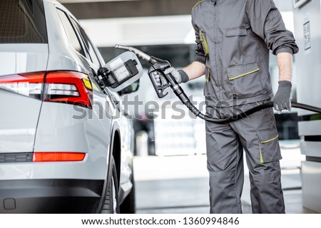 Gas station worker in workwear refueling luxury car with gasoline holding filling gun at the station