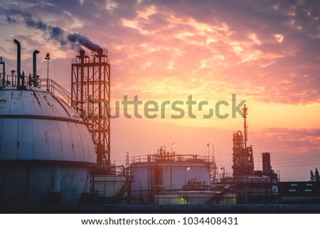 Gas storage sphere tank with smoke stack on sunset sky background, Industrial plant on sky sunset #1034408431