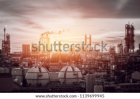 Gas storage sphere tanks in petrochemical industry or oil and gas refinery plant at evening, Manufacturing of petroleum industrial plant with gas column and smoke stacks on sunset sky background