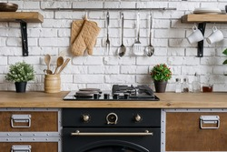 Gas stove, built in oven equipment, kitchenware supplies and houseplant in flower pot. Wooden kitchen in apartment with modern interior and new furniture