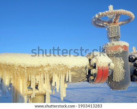 Gas valve and high pressure pipe. Oil and gas industry. Frozen icicles Stockfoto ©