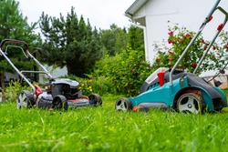 Gasoline and battery electric lawn mowers in the garden against the backdrop of a blooming garden, old and new grass mowing technologies