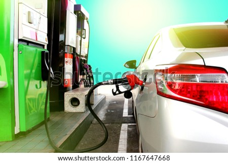 gasoline dispenser at petrol filling station.Fuel nozzle during refueling at a gas station.Fuel oil gasoline dispenser at petrol filling station.Holding fuel nozzle to refuel gasoline for car.