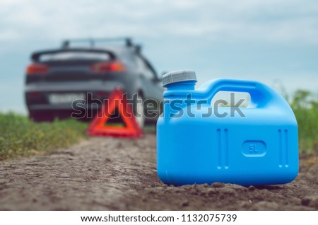 Gasoline finished concept. Not enough fuel. Red emergency triangle stop sign, empty canister for fuel and car on the road behind. Stockfoto ©