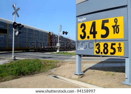 Gasoline price sign at a local station in rural Georgia, USA. Shows a train passing through railroad crossing. - stock photo