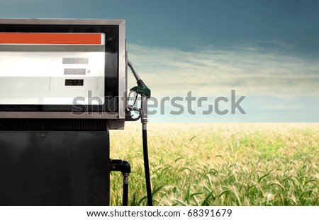 Gasoline pump with green meadow on the background