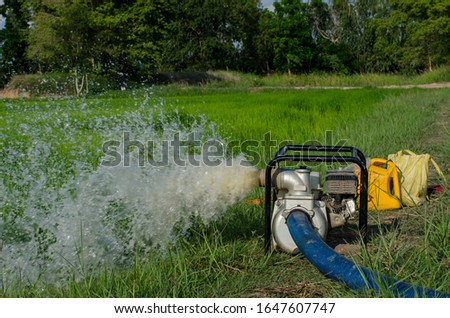 Photo of  Gasoline water pump recoil start and background is blue sky. Thai farmer are using to pump water for use in agriculture.