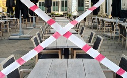 Gastronomy lockdown due to corona epidemic, closed restaurant terrace,chairs, tables and barrier tape, symbolic