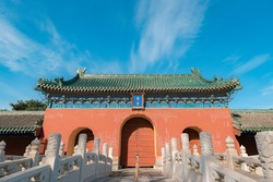 Gate and red wall of the ancient building in Zhaigong Temple against blue sky in Temple of Heaven, Beijing city, China. Chinese characters mean