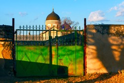 Gate into the yard of the church . View of church cupola over the fence