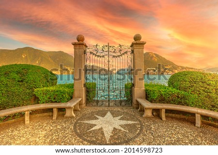 Gate on the Lugano Lake in the public Ciani park of Switzerland. Red sunset by the lakefront of Lugano city in Ticino canton. Park bench with wind rose of stones and with Monte San Salvatore mount. Zdjęcia stock ©