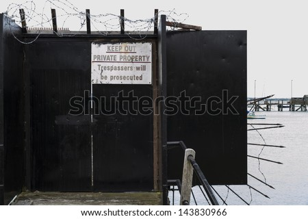Gate preventing access to jetty with warning sign -Private property keep out trespassers will be prosecuted
