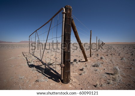 Gate somewhere in Namibia with fence disappearing in the distance.