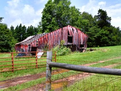 Gate to farm is open.  Dirt road passes in front of a dilapidated red, wooden barn.  Tin has been blown off roof.