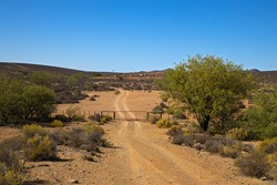 Gated dirt track to remote farm in barren region of Nama Karoo in Northern Cape, South Africa