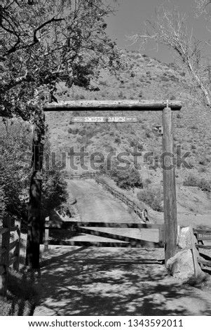 Gated road entrance leading to an old settlers ranch in the foothills of California