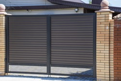 Gates of brown metal sheets. Roofing materials. Modern types of roofing materials.