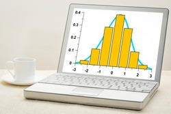 Gaussian, bell or normal distribution curve and histogram on laptop computer  with a cup of coffee