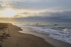 Gava Playa beach in Castelldefels, Barcelona, Spain. Bright sun, dark clouds, beautiful coastline. Large waves and fog in the background. Summer morning in nature, sunrise.
