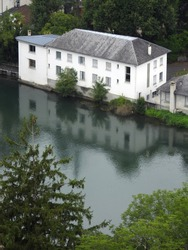 Gave de Pau river flowing through Lourdes with a town's building by the river bank. Hautes-Pyrenees, Occitanie, Southwest France