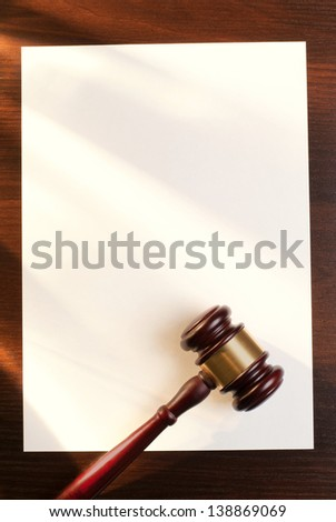 gavel and a sheet of paper on the brown table