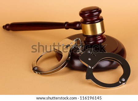 Gavel and handcuffs on beige background