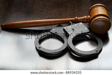 Gavel and handcuffs with keys on wooden background