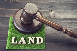Gavel and word LAND spelled in letters on artificial turf. Land disputes litigation metaphor