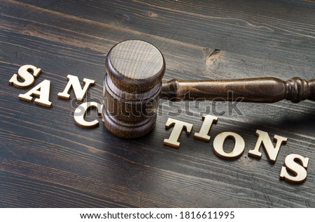 Gavel and word sanctions spelled in letters on table