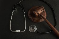 Gavel hammer of judge and stethoscop on black background. Law and medicine. Sentence on medical negligence