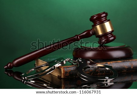 Gavel, handcuffs and book on law on green background