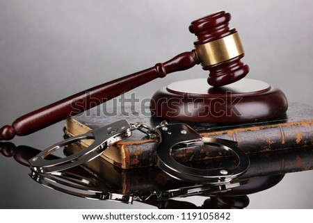 Gavel, handcuffs and book on law on grey background
