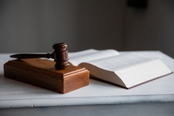 Gavel on block with legal textbook open