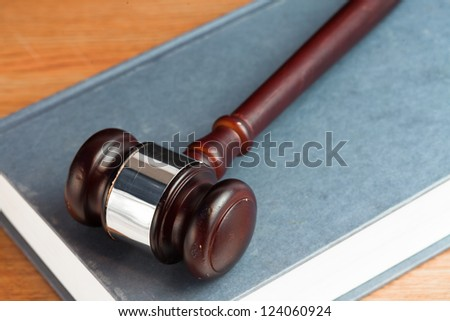 Gavel resting on a blue book on desk